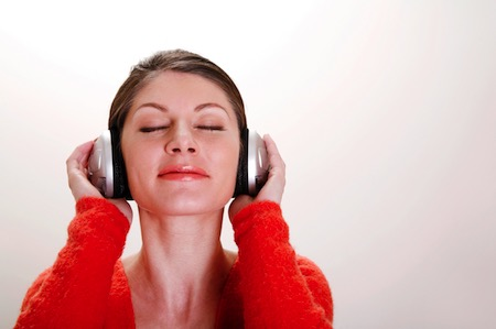 A woman listens to relaxing sounds on headphones