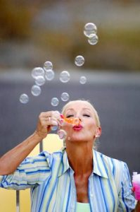 Happy woman blowing bubbles